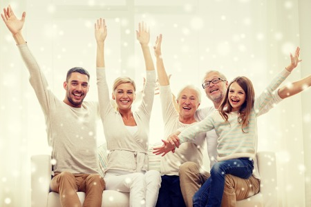 happy senior: family, happiness, generation and people concept - happy family sitting on sofa and rising hands at home Stock Photo