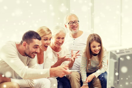 television show: family, happiness, generation and people concept - happy family sitting on sofa and watching tv at home Stock Photo