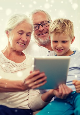 computer generation: family, generation, technology and people concept - smiling grandparents and grandson with tablet pc computer at home Stock Photo