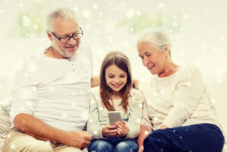 family couch: family, generation, technology and people concept - smiling grandfather, granddaughter and grandmother with smartphone sitting on couch at home