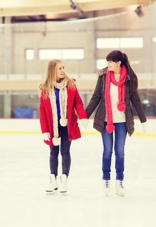 iceskates: people, women, friendship, sport and leisure concept - two happy girls friends on skating rink Stock Photo