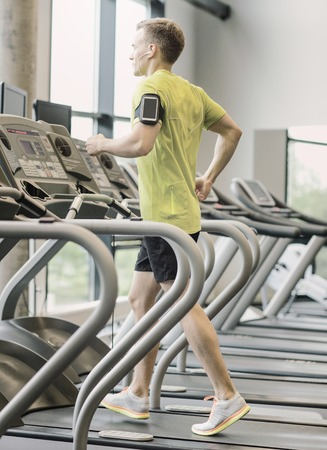 sport, fitness, lifestyle, technology and people concept - man with smartphone and earphones exercising on treadmill in gym Stock Photo