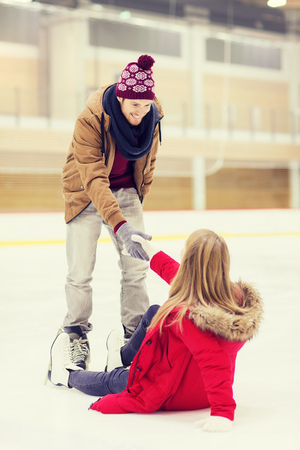 boy skating: people, friendship, sport and leisure concept - smiling man helping women to rise up on skating rink