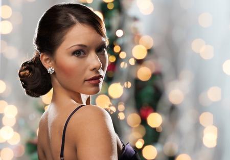 navidad elegante: gente, fiestas, joyas y el concepto de lujo - cara de la mujer con el pendiente de diamantes en Navidad las luces del árbol de fondo
