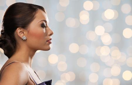 perfil de mujer rostro: gente, fiestas, joyas y el concepto de lujo - cara de la mujer con el pendiente de diamantes sobre fondo de las luces