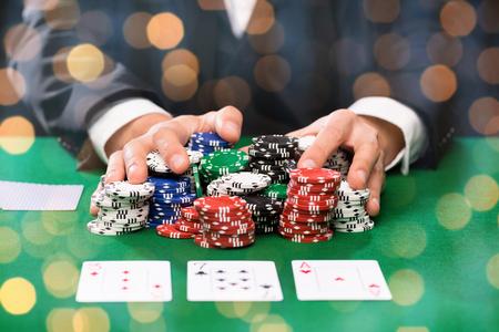 cartas poker: casino, juegos de azar, el póquer, la gente y concepto de entretenimiento - primer plano de jugador de póquer con cartas y fichas de casino en el vector verde sobre fondo de las luces de fiesta Foto de archivo