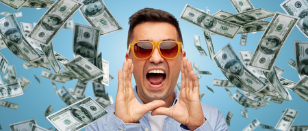business, finance, emotions, and people concept - face of angry middle aged latin man in shirt and sunglasses shouting over blue background with heap of falling dollar money