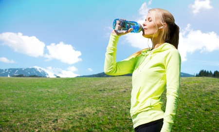 people, fitness, sport and healthy lifestyle concept - happy woman drinling water from bottle after workout over natural background Stockfoto