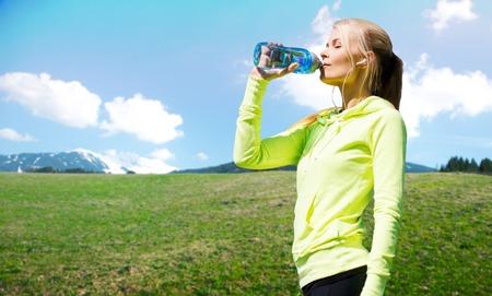 mensen, fitness, sport en een gezonde levensstijl concept - tevreden vrouw drinling water uit de fles na de training over natuurlijke achtergrond Stockfoto