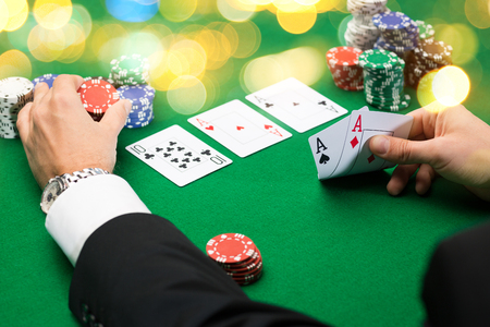 casino, gambling, poker, people and entertainment concept - close up of poker player with playing cards and chips at green casino table over holidays lights background Stockfoto