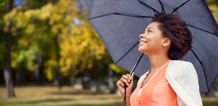 autumn city: business, weather, season, fall and people concept - young smiling african american woman with umbrella over autumn park background