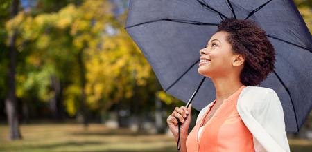 lluvia: negocio, clima, la estación, el otoño y el concepto de la gente - Mujer africana sonriente joven americano con el paraguas sobre el fondo del parque del otoño
