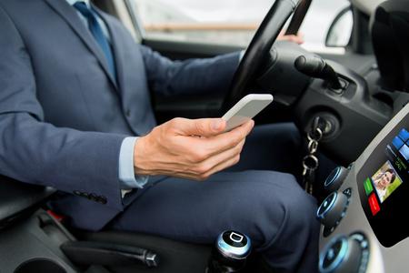 hombre conduciendo: transporte, viaje de negocios, la tecnolog�a y el concepto de la gente - cerca del hombre joven con el tel�fono inteligente de conducci�n de coches y recepci�n de llamada entrante de la mujer en la pantalla de ordenador de a bordo