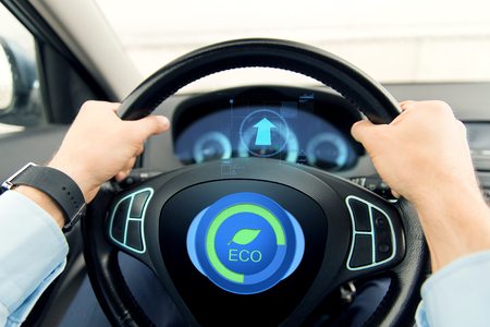 transport, business trip, technology and people concept - close up of male hands holding car wheel and driving in eco mode