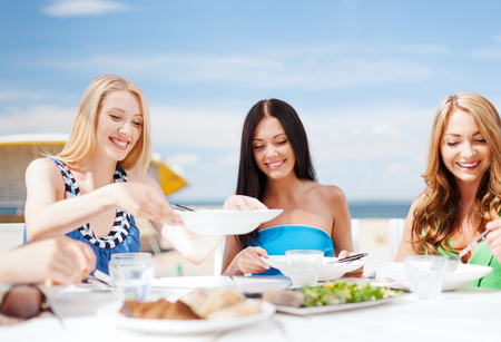cafe: summer holidays and vacation - girls eating and drinking in cafe on the beach