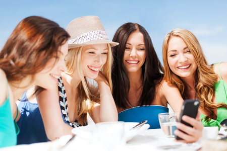 people laughing: summer holidays, vacation and technology - girls looking at smartphone in cafe on the beach