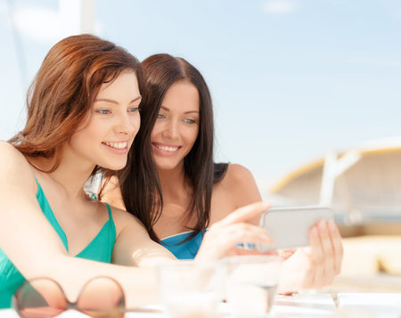holiday summer: summer holidays, vacation and technology concept - girls looking at smartphone in cafe on the beach