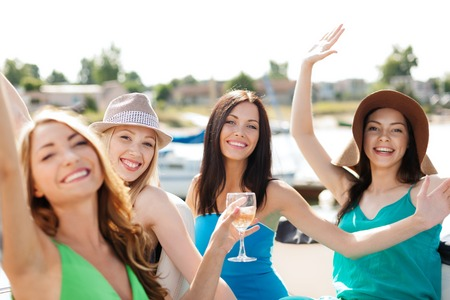 boat party: summer holidays and vacation - girls with champagne glasses on boat or yacht Stock Photo