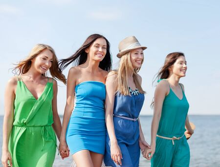 summer dress: summer holidays and vacation concept - girls walking on the beach Stock Photo