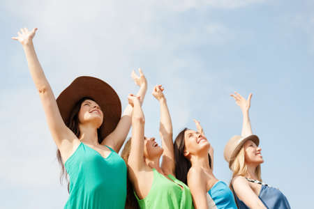 dress up: summer holidays and vacation concept - smiling girls with hands up on the beach