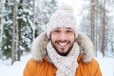 young men: season, christmas and people concept - happy smiling young man in snowy winter forest