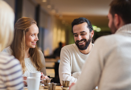 drink coffee: people, leisure, communication, eating and drinking concept - happy friends meeting and drinking tea or coffee at cafe