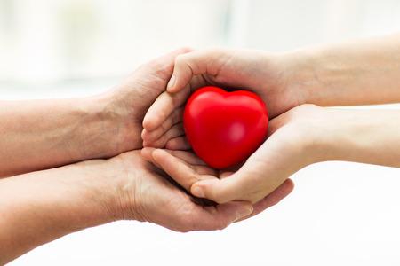 salud: las personas, la edad, la familia, el amor y el cuidado de la salud concepto - cerca de la mujer mayor y mujer joven manos sosteniendo el corazón rojo