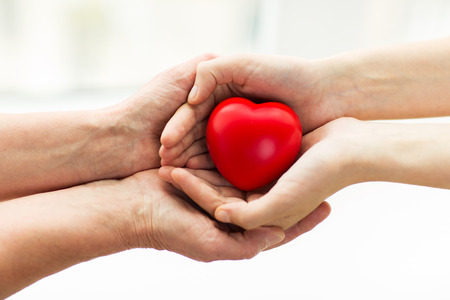 old carer: people, age, family, love and health care concept - close up of senior woman and young woman hands holding red heart