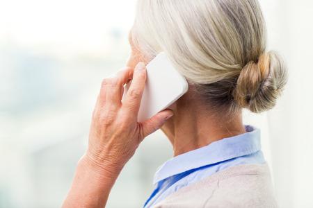 mujeres ancianas: la tecnología, la comunicación, la edad y el concepto de la gente - cerca de la mujer mayor con llamadas de teléfonos inteligentes en el hogar Foto de archivo