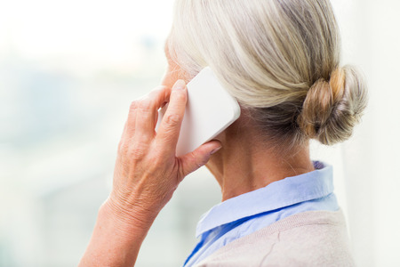 old women: technology, communication, age and people concept - close up of senior woman with smartphone calling at home