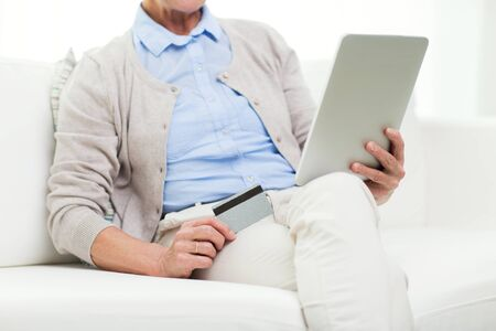 shopper: technology, online shopping, age and people concept - close up of senior woman with tablet pc computer and credit or bank card at home