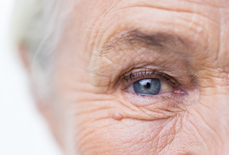 closeup: age, vision and old people concept - close up of senior woman face and eye