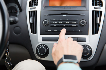 transport, road trip, car driving, technology and people concept - close up of male hand turning on radio on control panel system in car Standard-Bild