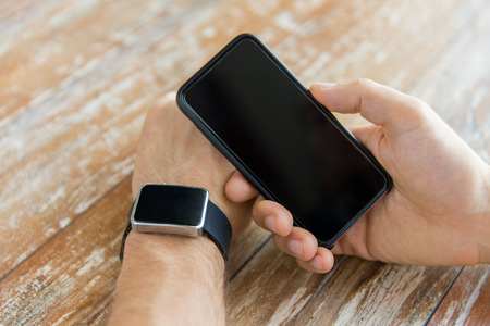 cellular: business, technology and people concept - close up of male hand holding smart phone and wearing watch at home