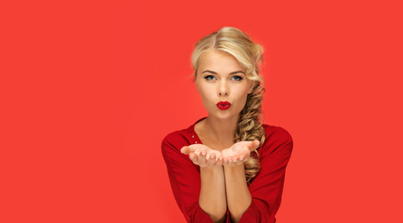 kisses: people, holidays, christmas, valentines day and advertisement concept - lovely woman in red dress blowing something on palms of her hands over red background
