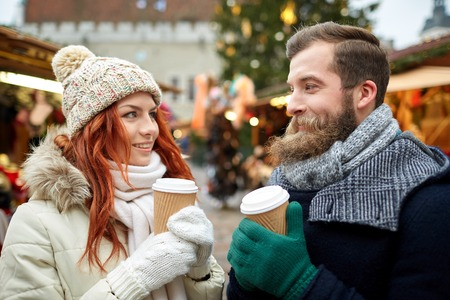 happy christmas: holidays, winter, christmas, hot drinks and people concept - happy couple of tourists in warm clothes drinking coffee from disposable paper cups in old town