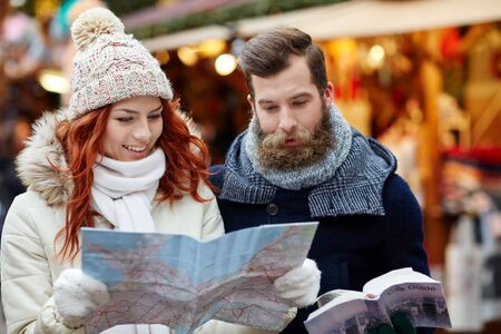 tourism: holidays, winter, christmas, tourism and people concept - happy couple in warm clothes with map and city guide in old town