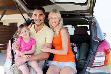 transport, leisure, road trip and people concept - happy happy family with little girl sitting on trunk of hatchback car at home parking space