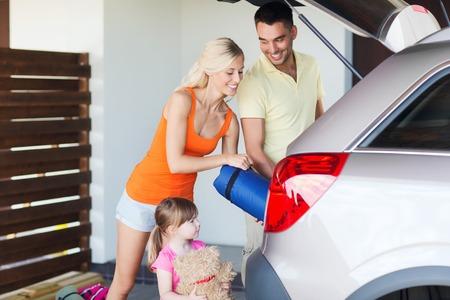 tronco: transporte, ocio, viajes, viaje por carretera y la gente concepto - felices cosas de embalaje de la familia en el coche en el aparcamiento casa