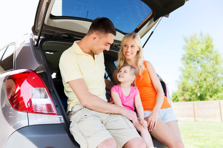 hatchback: family , transport, leisure, road trip and people concept - happy man, woman and little girl sitting on trunk of hatchback car and talking outdoors Stock Photo