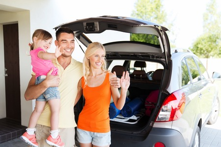 transport, leisure, road trip and people concept - happy family with little girl sitting on trunk of hatchback car and waving hands at home parking space