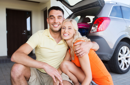 motor car: transport, leisure, family and people concept - happy couple hugging at home car parking space Stock Photo