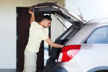 tronco: viaje por carretera, transporte, propiedad de ocio y la gente privada concepto - hombre joven con tronco de coche abierto en plaza de aparcamiento