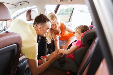car seat: family, transport, safety, road trip and people concept - happy parents talking to little girl in baby car seat