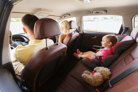 family, transport, safety, road trip and people concept - happy parents with little child driving in car Standard-Bild