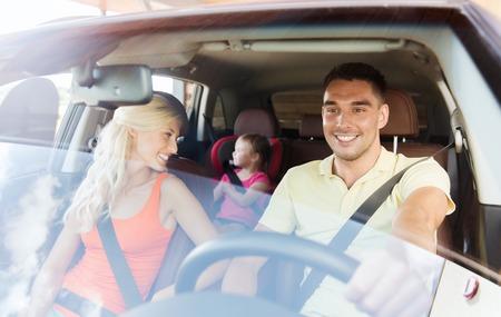 transport: familj, transport, säkerhet, väg resa och folk koncept - lycklig man och kvinna med litet barn körning i bil