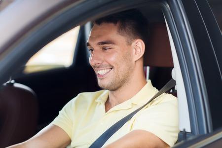 manejando: viaje por carretera, el transporte, el ocio y el concepto de la gente - hombre feliz que conduce el coche sonriendo al aire libre