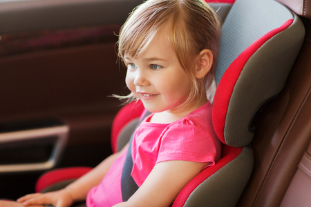 car safety: transport, safety, childhood road trip and people concept - happy little girl sitting in baby car seat