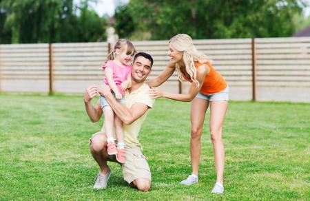 pareja abrazada: la familia, la felicidad, la adopción y la gente concepto - familia feliz abrazando al aire libre
