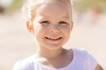 face of baby: summer, childhood, happiness and people concept - happy beautiful little girl portrait outdoors Stock Photo